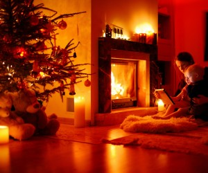 Young mother and her daughters using a tablet pc by a fireplace